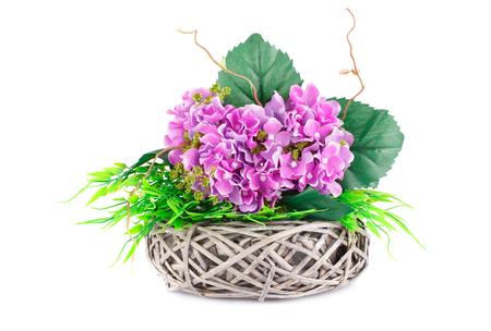 Pink fabric flowers in wicker basket isolated on white background.