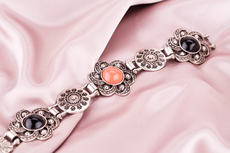 Ancient style bracelet with colorful stones on fabric background.