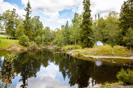 Landscape with forest, pond and tent in Norway.