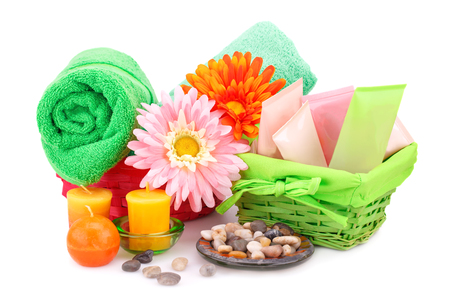 Spa set with towels, creams, lotions, candles, stones and flowers isolated on white background.
