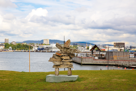 Oslo, Norway-August 13, 2014 - Coastline with stone statue, city and hills.
