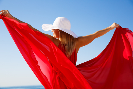 Blond woman in the red dress with the white hat at the beach in Cyprus. Imagens - 101908447