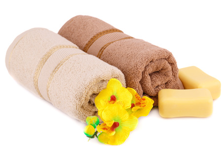 Rolled towels, soaps and flowers isolated on white background.
