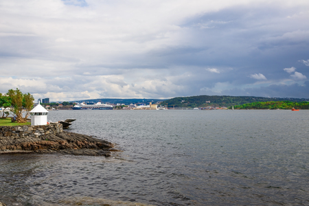 Oslo, Norway-August 13, 2014 - Coastline with ship, hills and forest.