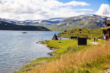 Norway-August 15, 2014 -  Landscape with mountain, lake, houses and people in Norwegian rural place. Editorial