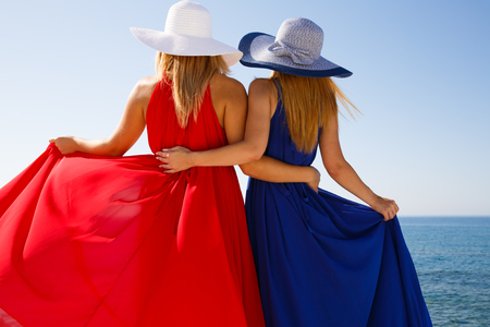 Blond women in the red and blue dresses at the beach in Cyprus. 스톡 콘텐츠