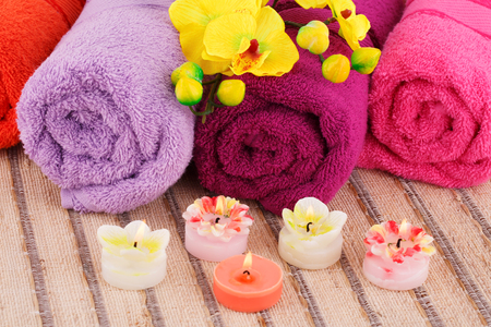 Spa set with towels, candles and flowers on bamboo background.