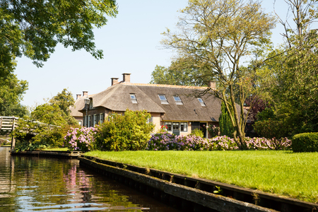 The thatched roof house with beautiful garden in fairy-tale village Giethoorn in The Netherlands. Redactioneel
