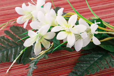 White artificial flowers on cloth background, closeup picture.