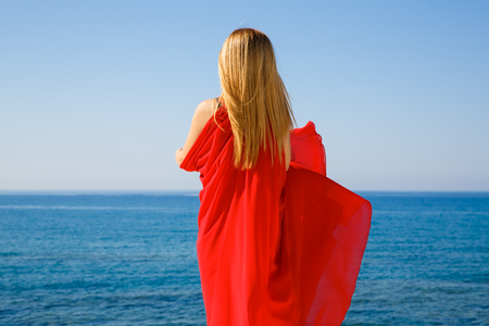 Pretty blond woman in the red dress at the beach in Cyprus. Imagens