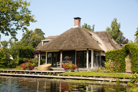 The thatched roof house with beatiful garden in fairytale village Giethoorn in The Netherlands.