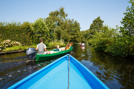 Giethoorn, Netherlands, August 20, 2015 - The unknown tourists on the sightseeing boats in the Dutch fairytale village.