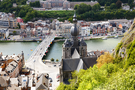 Dinant, Belgium - The top view of The Collegiate Church of Notre-Dame, Charles de Gaulle bridge over Meuse river and Belgian old city houses.