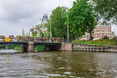 Amsterdam, Netherlands-August 18, 2015-Canal with bridge and buildings, view from the water.