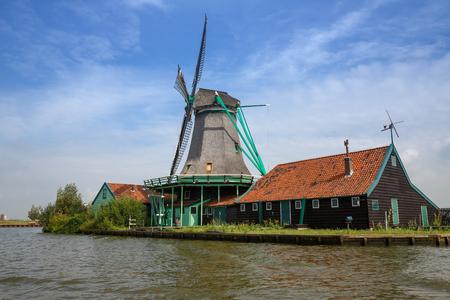 Traditional, authentic dutch windmill at the river Zaam in Zaanse Schans village.