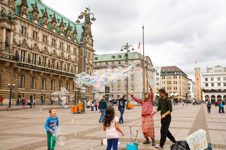 Hamburg, Germany - August 15, 2016 - Unknown street artists make big soap bubbles in the market square at Rathaus (Town Hall).