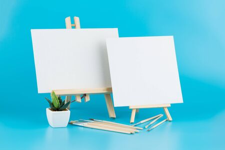 Two wooden blank easels with brushes and plant on blue background. Stock Photo