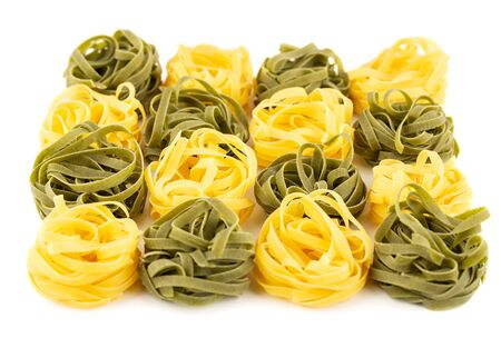 The heap of tagliatelle pasta isolated on white background.