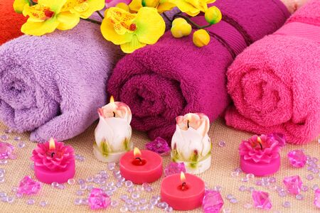 Spa set with towels, candles and flowers on canvas background.