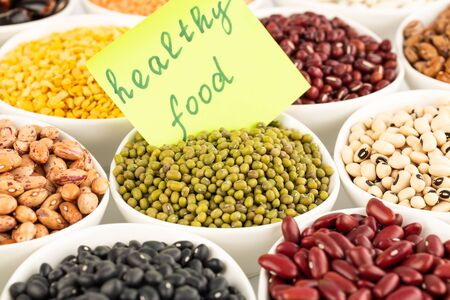 The collection of different beans and peas in the ceramic bowls with notice healthy food. Stok Fotoğraf