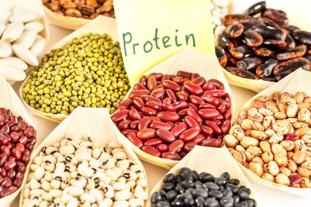 The collection of different beans in the bamboo bowls with the notice protein on paper.