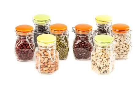The collection of different beans in the glass jars isolated on a white background.