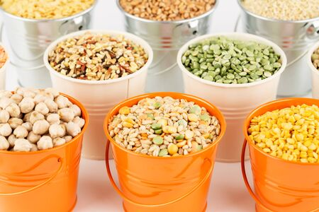 The collection of different groats in the metallic buckets. Quinoa, wheat, split peas, chickpea, and lentil.