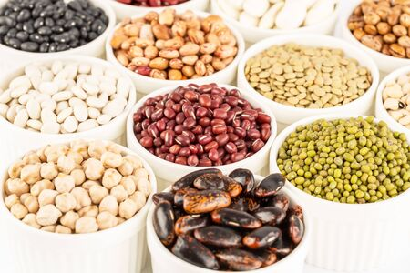 The collection of different beans and lentils in the ceramic bowls.