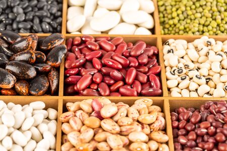 The collection of different beans in the wooden box.