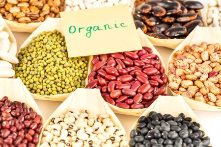 The collection of different beans in the bamboo bowls with the notice organic on paper.