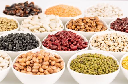 The collection of different beans in the ceramic bowls on a white background.