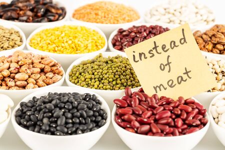 The collection of different beans and peas in the ceramic bowls with notice instead of meat.