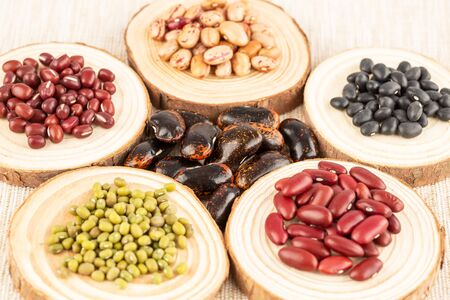 The collection of different beans on the wooden round boards.