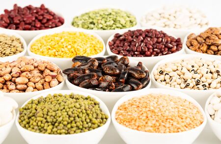 The collection of different beans and peas in the ceramic bowls.