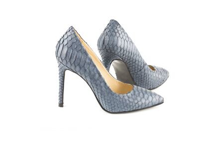 The pair of stylish high heels python leather shoes isolated on white background.