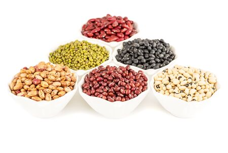 The collection of different beans in the ceramic bowls isolated on a white background.