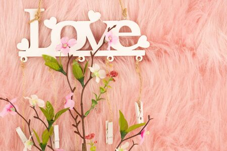White wooden word love and flowers on pink fur background.
