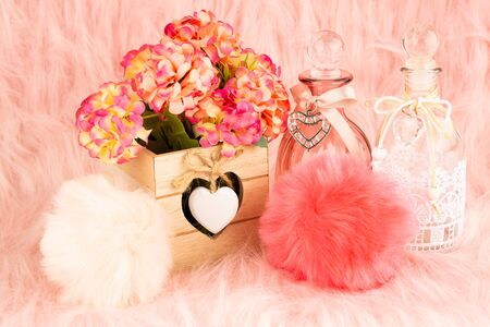 Beige wooden box, flowers, bottles and fluffy pompons on pink fur background. Foto de archivo