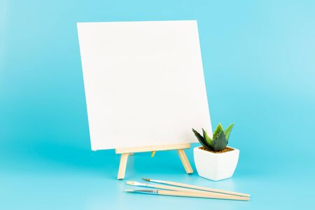 Wooden easel with blank canvas and brushes on blue background.