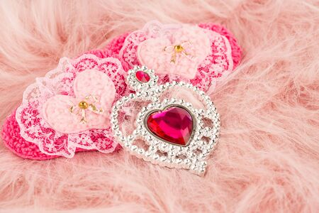 Jewelry and fabric hearts with stones on pink fur background. Imagens