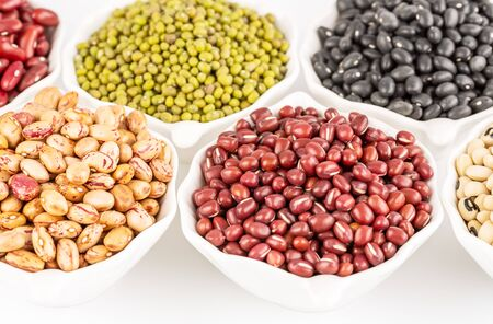 The collection of different beans in the ceramic bowls.