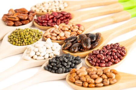 Various beans in the wooden spoons on a white background.