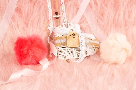 White wooden heart with ribbon and fluffy balls on pink fur background.