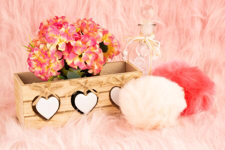 Beige wooden box, flowers, bottle and fluffy pompons on pink fur background.