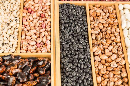 Different beans in the wooden box. Borlotti, black eyed, scarlet runner, black turtle.