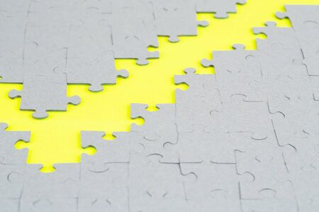 Unfinished jigsaw puzzle pieces on yellow background. Stock Photo