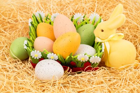 Easter colorful eggs in basket and yellow bunny on straw background. Stock Photo - 137259409