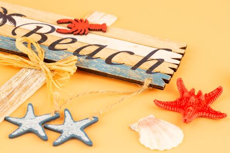 Wooden sign beach, starfish and shell on yellow background.