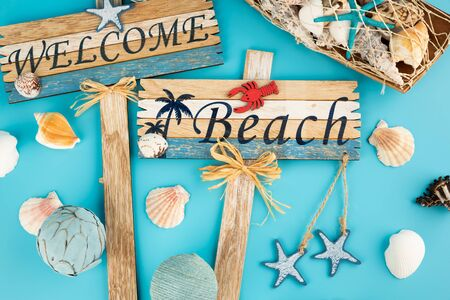 Wooden signs welcome beach and shells on blue background.