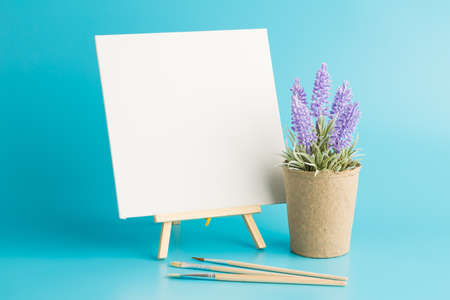 Wooden easel with blank canvas, brushes and lavender flowers on blue background. Archivio Fotografico